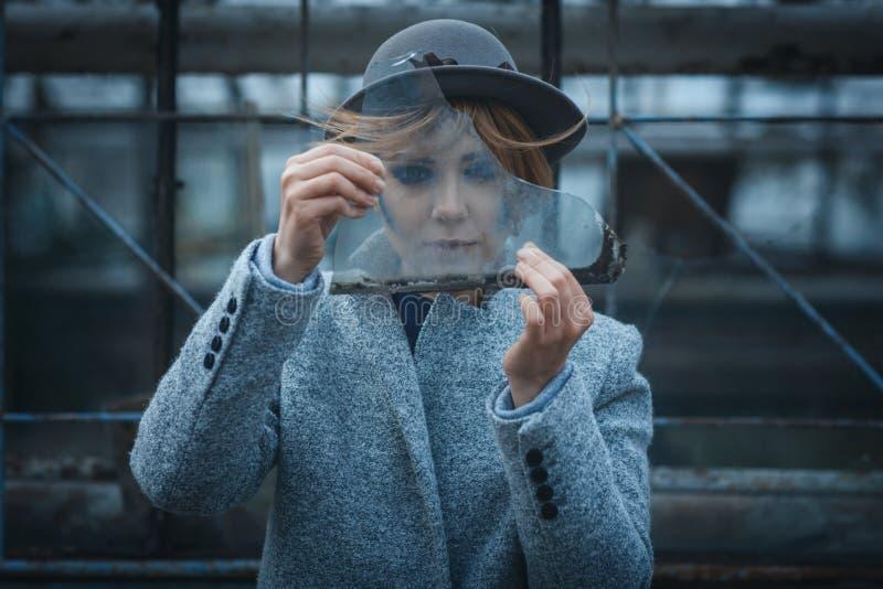 A menina olha através de uma parte de vidro foto de stock royalty free