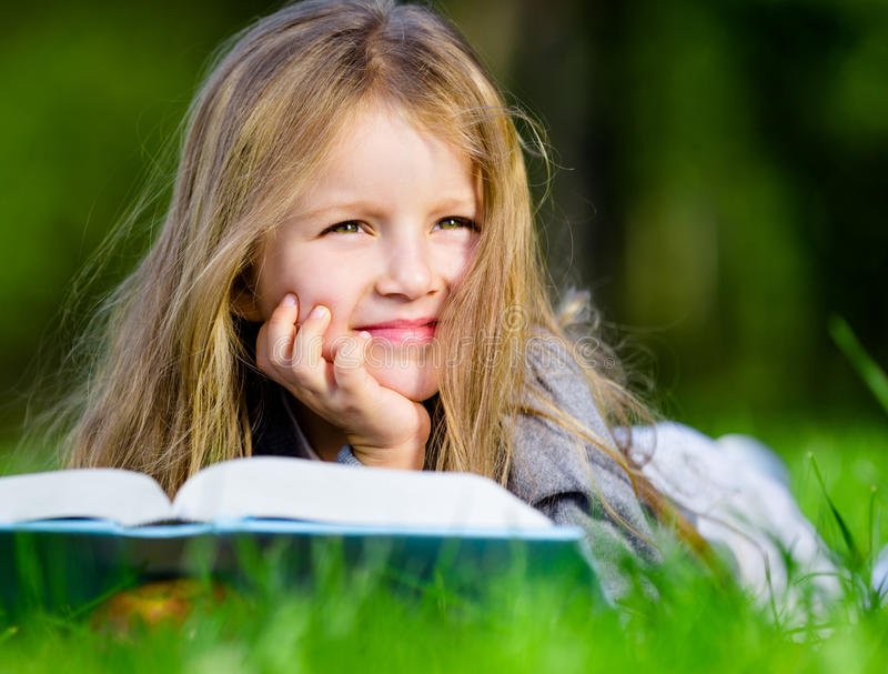 A menina olha através do livro que encontra-se na grama verde fotos de stock royalty free