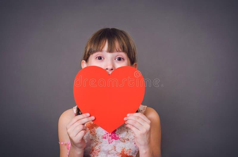 A menina olha de debaixo do coração fotos de stock
