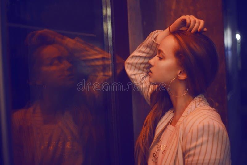 A menina olha na reflexão da janela Uma menina está perto da entrada ao clube do restaurante Retrato da noite Brunette fotografia de stock