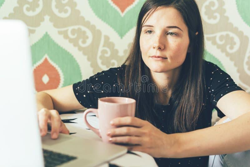 A menina olha no monitor do portátil imagem de stock