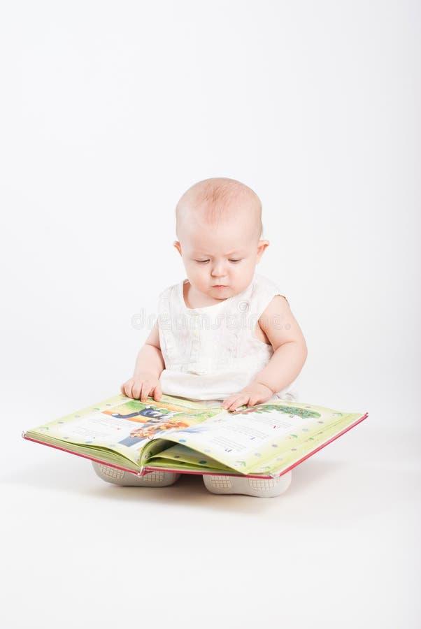 A menina olha o livro de crianças imagens de stock