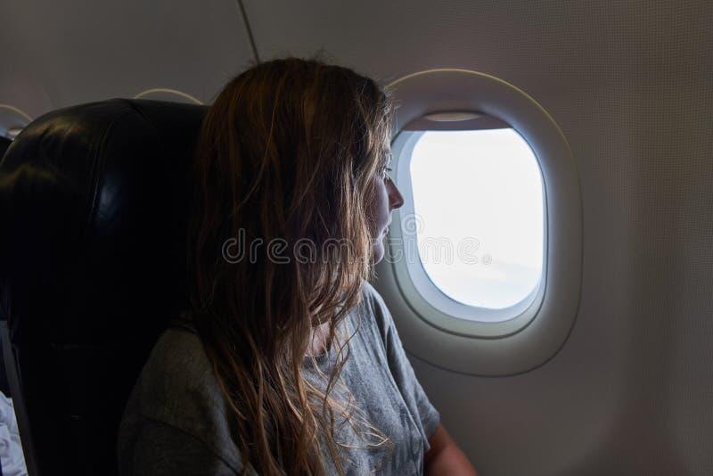 A menina olha para fora a janela do plano fotos de stock royalty free