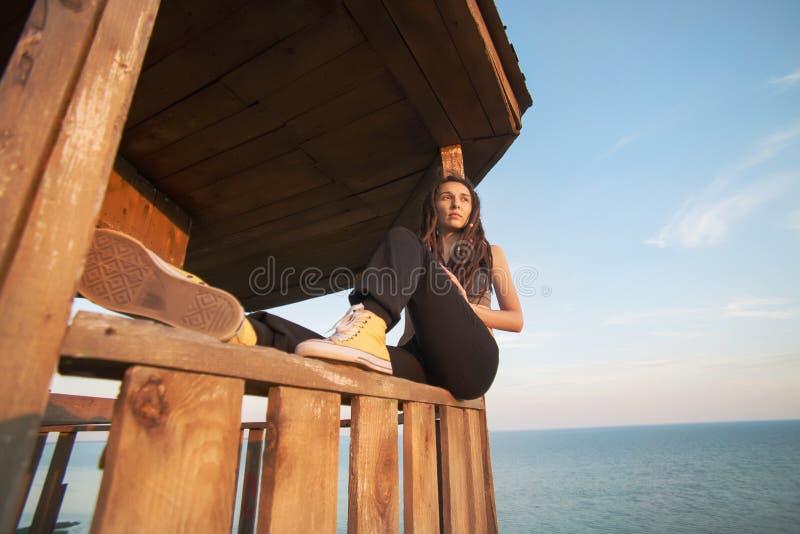 A menina olha pensativamente na distância de madeira fotografia de stock