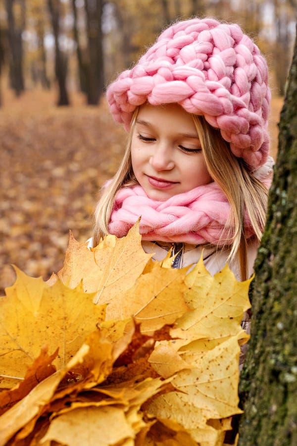 a menina olha sonhadoramente um ramalhete das folhas de bordo imagens de stock royalty free