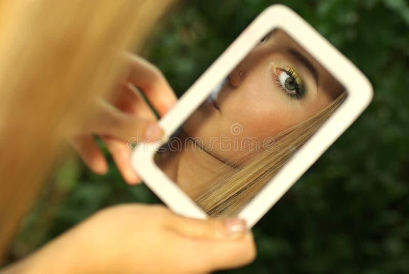 A menina olha sua reflexão no espelho fotos de stock
