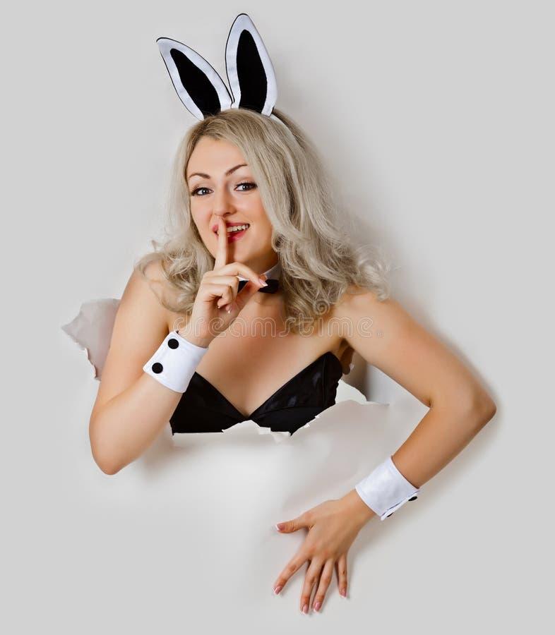 Menina - olhares brincalhão do coelho 'sexy' de um furo imagem de stock