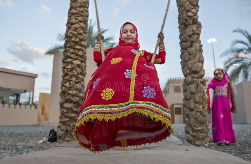 menina omanense na roupa tradicional em um balanço imagens de stock royalty free