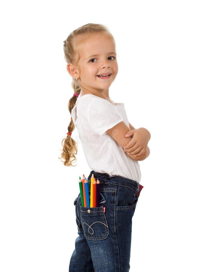 Menina orgulhosa pequena com os lápis em seu bolso imagem de stock royalty free