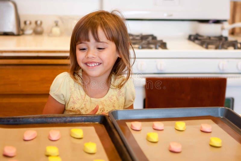 A menina orgulhosa terminou colocar a massa da cookie na folha de cookie foto de stock