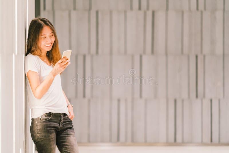 Menina ou estudante universitário asiática bonita nova que usa o smartphone e o sorriso Estilo de vida moderno, conceito da tecno foto de stock