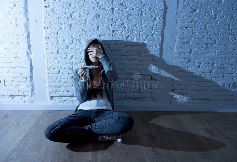 Menina ou jovem mulher nova do adolescente em choque assustado após o teste de gravidez positivo imagens de stock