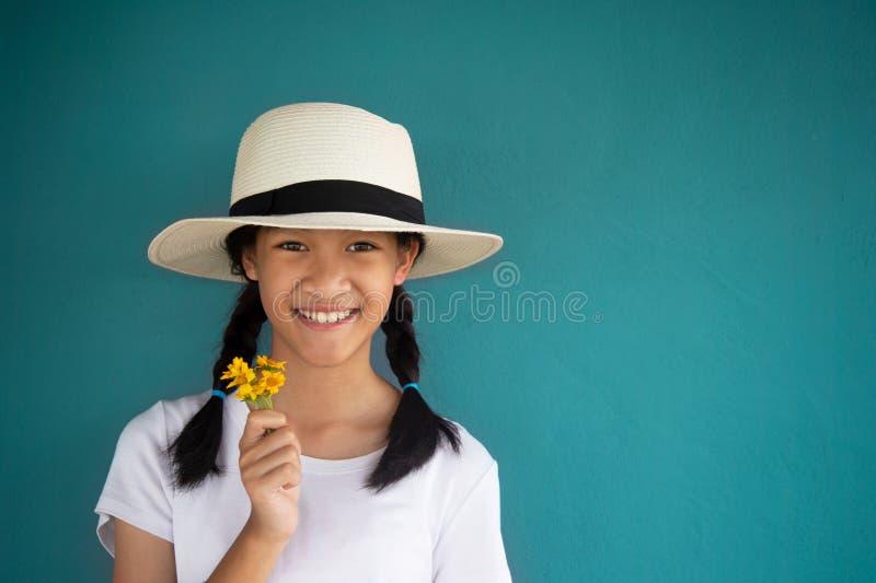 menina ou jovens mulheres de 11s Ásia no t-shirt branco e no chapéu do verão que guardam a flor selvagem amarela da mola na pared imagens de stock royalty free