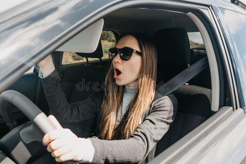 A menina ou o motorista no carro são surpreendida ou assustado foto de stock