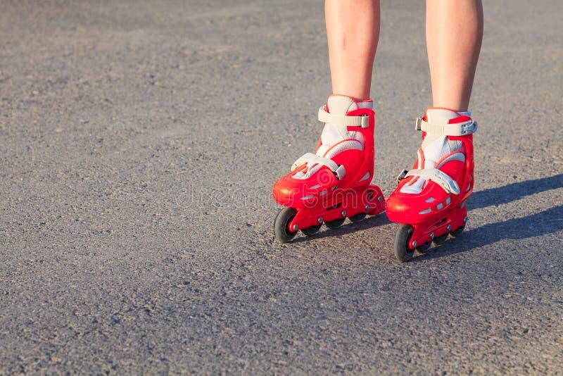 Menina ou um menino porque ou são rollerskating imagem de stock