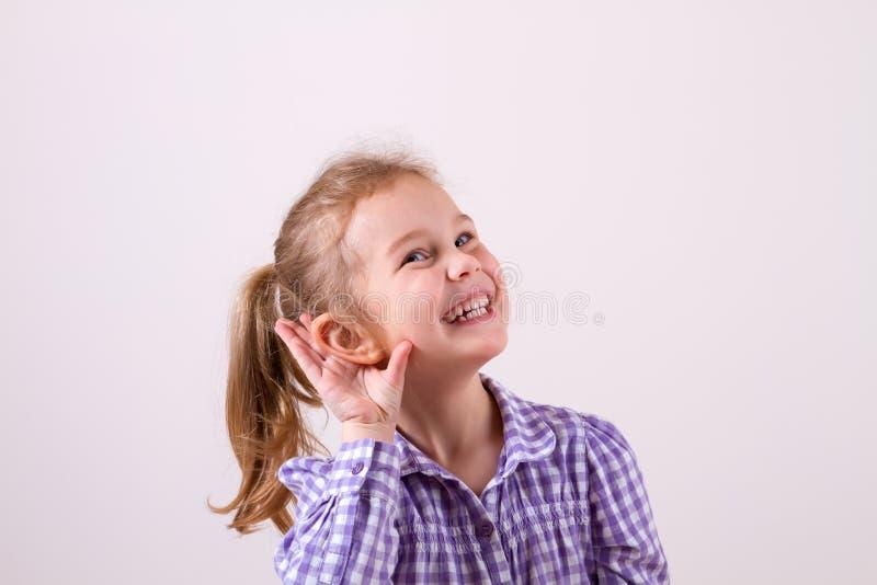 A menina põe uma mão à orelha para ouvir-se melhor fotos de stock