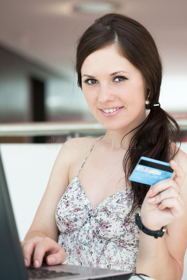 A menina paga a compra através do Internet foto de stock royalty free