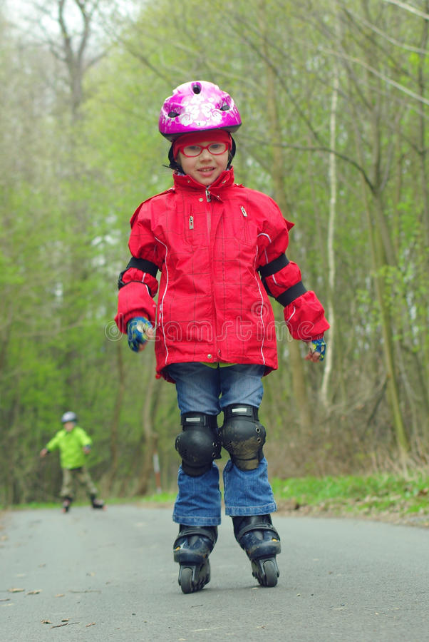 A menina patina patinagem inline ao ar livre imagens de stock royalty free