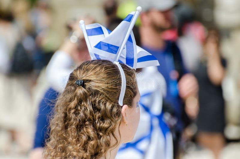 A menina patriótica com a bandeira israelita em sua cabeça comemora o dia de Israel Independence imagem de stock royalty free