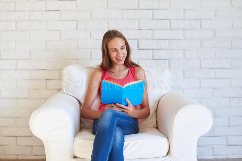 Menina pegada lendo um livro na sala com a parede de tijolo branca imagens de stock royalty free