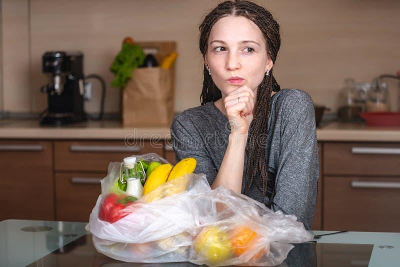 A menina pensa aquela para recusar usar um saco de plástico para comprar produtos Proteção ambiental e o abandono do plástico fotografia de stock