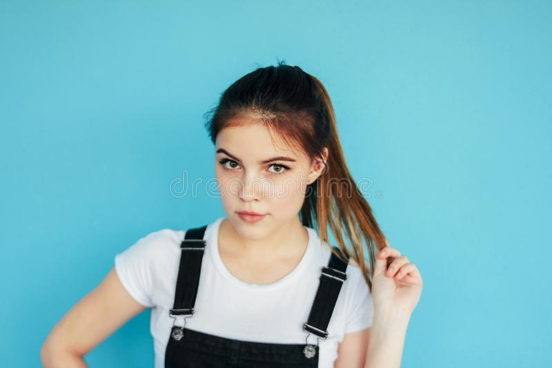 Menina pensativa bonita com cabelo longo escuro no t-shirt branco isolado no fundo azul fotografia de stock