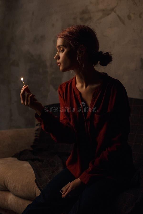 A menina pensativa bonita na camisa vermelha senta-se na sala escura, ilumina-se acima de matchstick ardente e guarda-se a caixa  imagem de stock royalty free