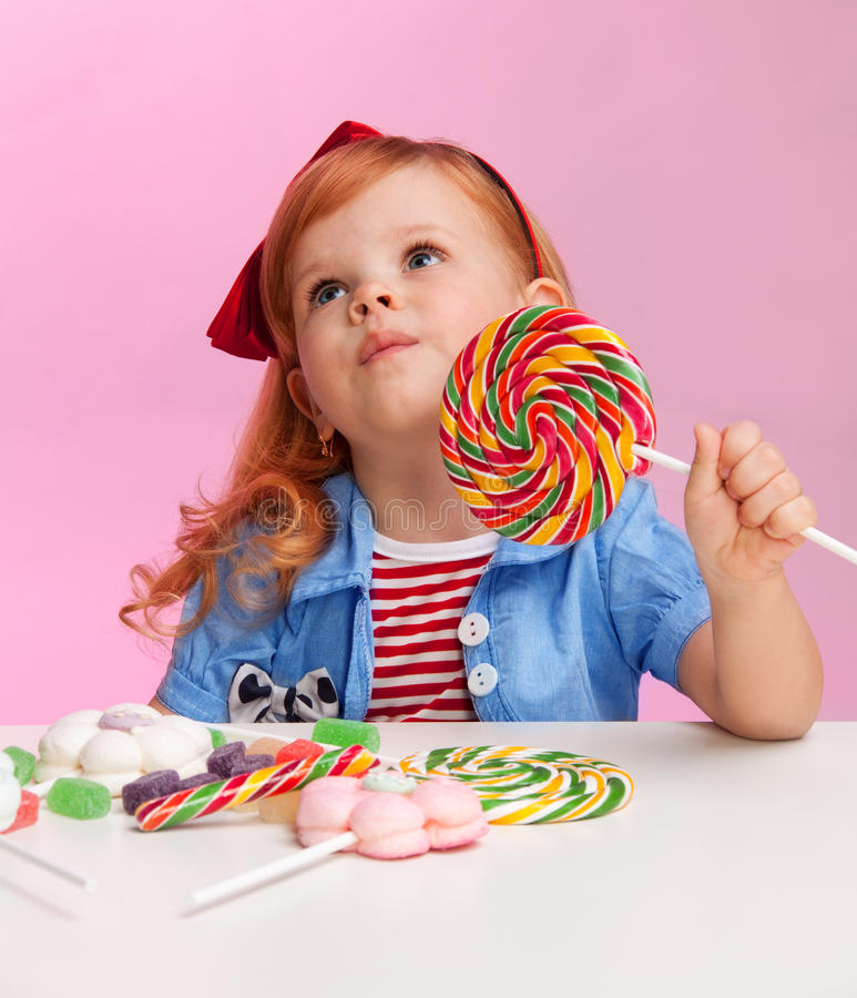 Menina pensativa com lollipop fotos de stock