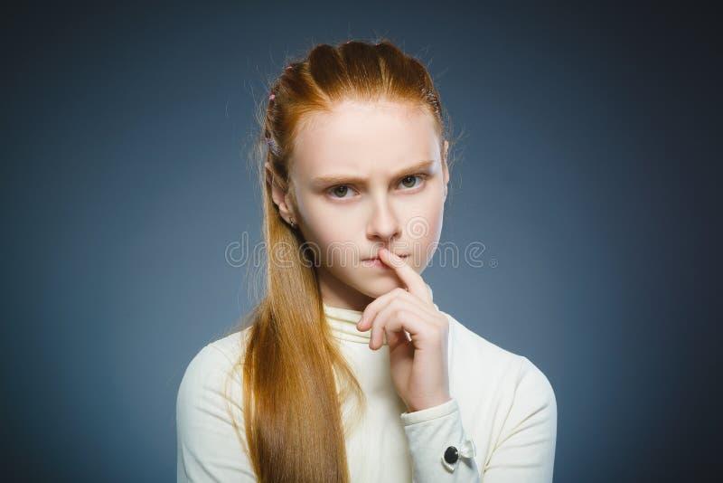 Menina pensativa do close up com mão na cabeça no cinza imagem de stock