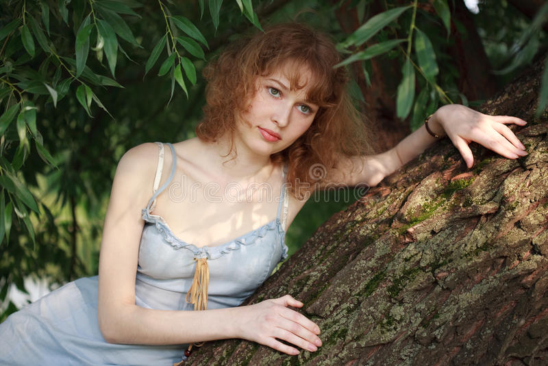 Menina pensativa em uma árvore fotografia de stock royalty free