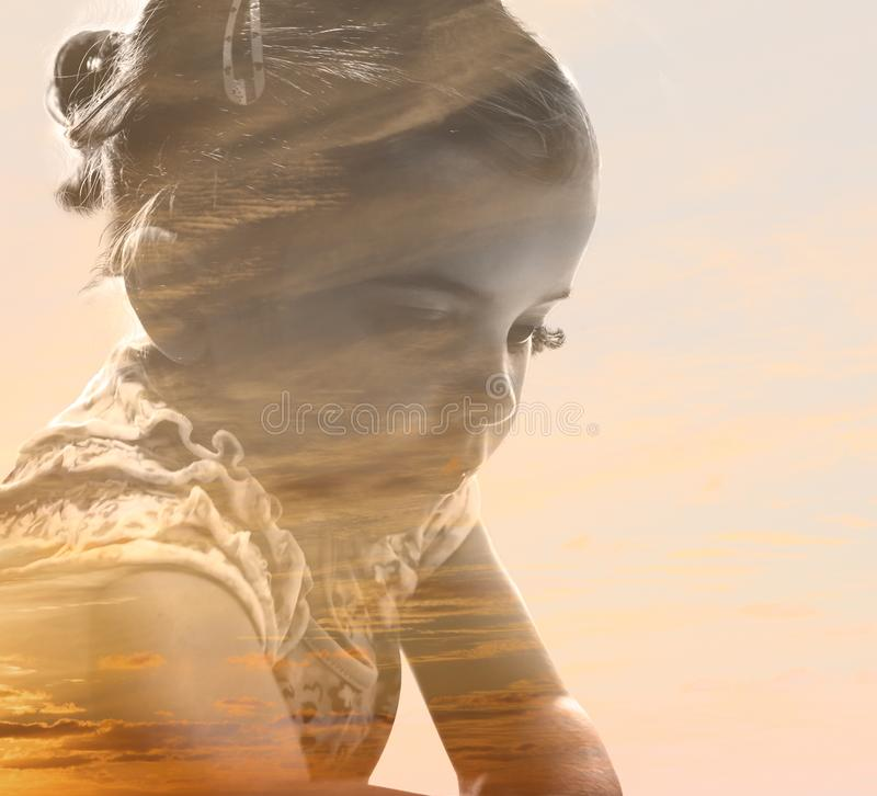 Menina pensativa fundida com o céu do por do sol foto de stock royalty free