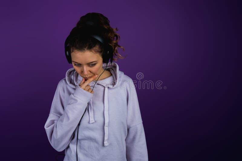 Menina pensativa que escuta a música triste sobre o hoodie dos fones de ouvido em um fundo roxo fotografia de stock