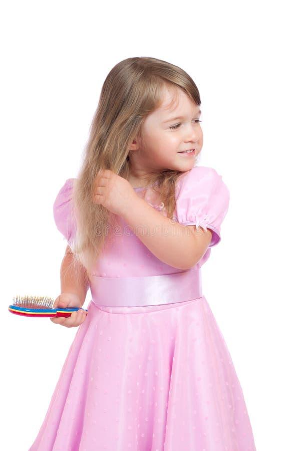 A menina penteia o cabelo imagem de stock
