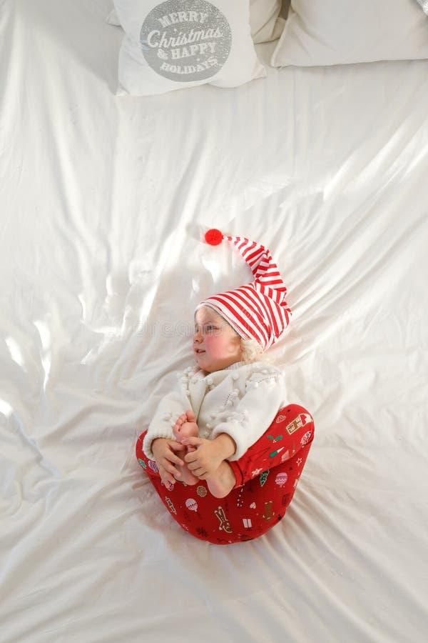A menina pequena adorável repousante nos pyjamas, nos pés dos aumentos e nos estiramentos na cama, mentiras no roupa de cama bran imagens de stock royalty free