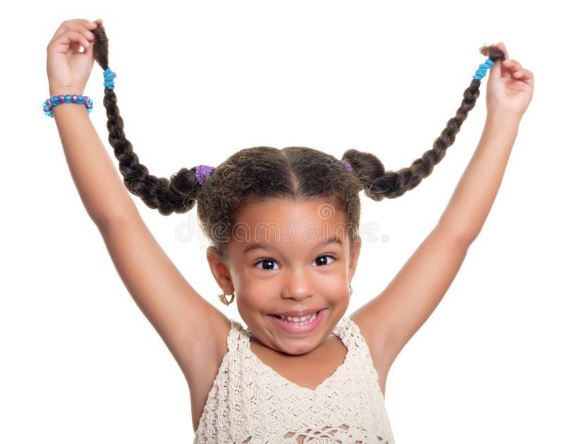 Menina pequena afro-americano bonito que ri e que puxa seu cabelo mim fotos de stock royalty free