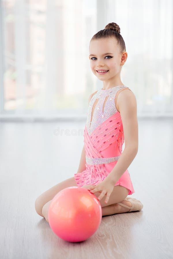 Menina pequena bonita da ginasta no vestido cor-de-rosa do sportswear, elemento da ginástica das artes de palco com a bola na cla foto de stock royalty free