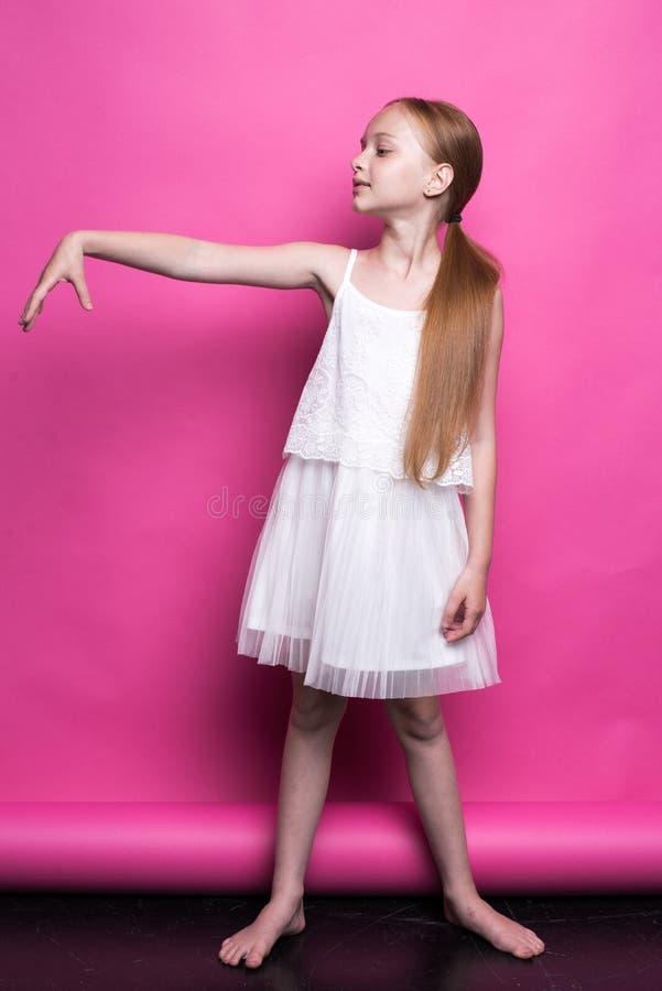 Menina pequena bonita do ruivo no vestido branco que levanta como o modelo no fundo cor-de-rosa imagem de stock royalty free