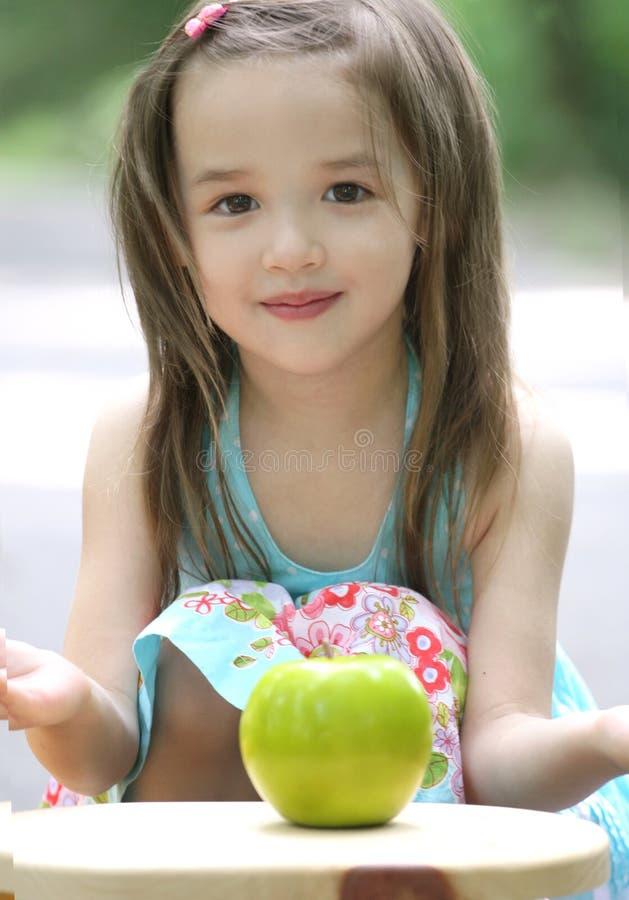 Menina pequena bonito da criança com Apple fotos de stock