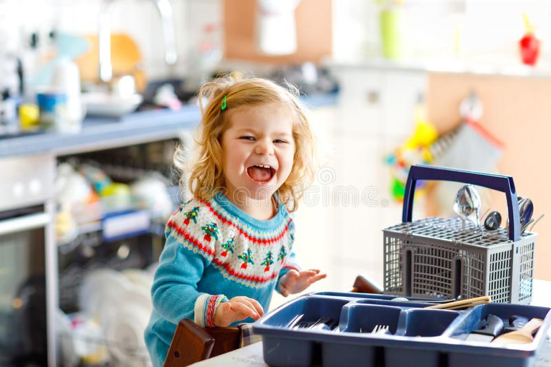 Menina pequena bonito da criança que ajuda na cozinha com máquina de lavar do prato Criança loura saudável feliz que classifica f fotografia de stock royalty free