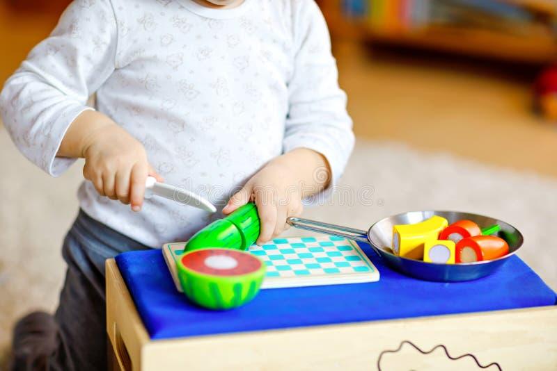 Menina pequena bonito da criança que joga em casa com os brinquedos de madeira do eco Criança entusiasmado saudável feliz que cor imagem de stock royalty free
