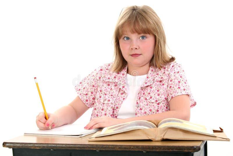 Menina pequena bonito da escola que senta-se na mesa com livros imagens de stock