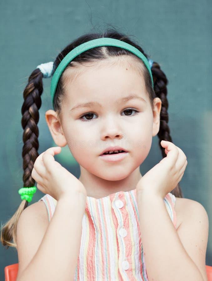 Menina pequena bonito de аsian com tranças imagens de stock