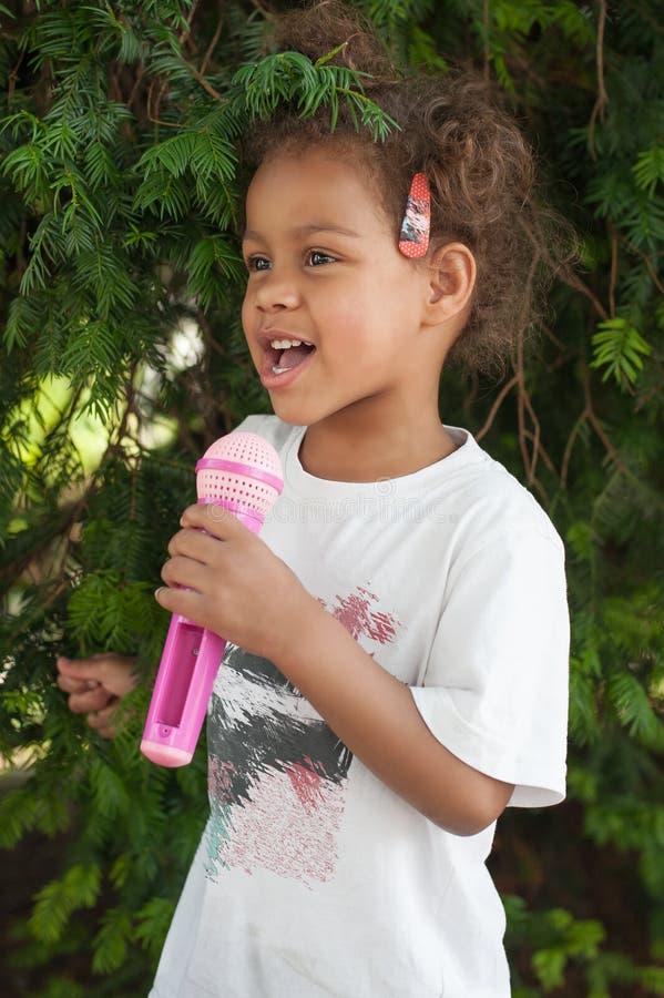 Menina pequena bonito do cantor que canta no microfone no pa da cidade fotografia de stock