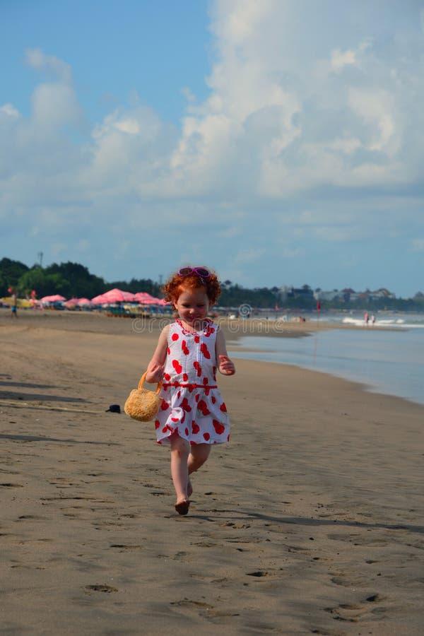 A menina pequena bonito do ruivo corre na praia de Bali imagem de stock