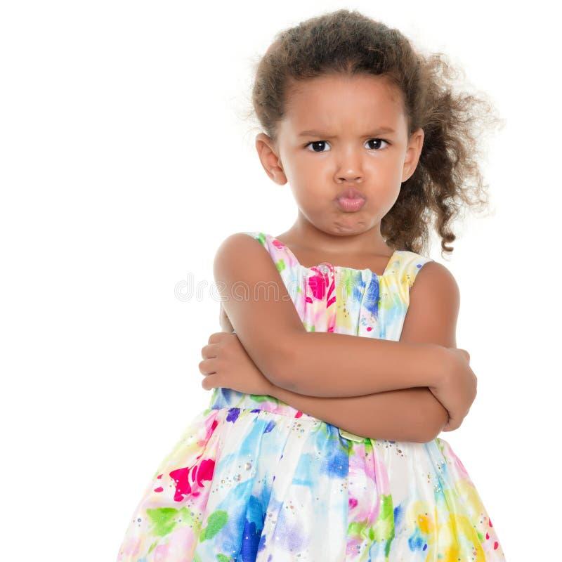 Menina pequena bonito que faz uma cara irritada engraçada imagens de stock