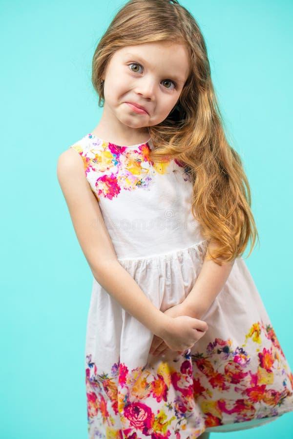 Menina pequena bonito que veste um vestido do verão das flores isolado no azul imagens de stock royalty free