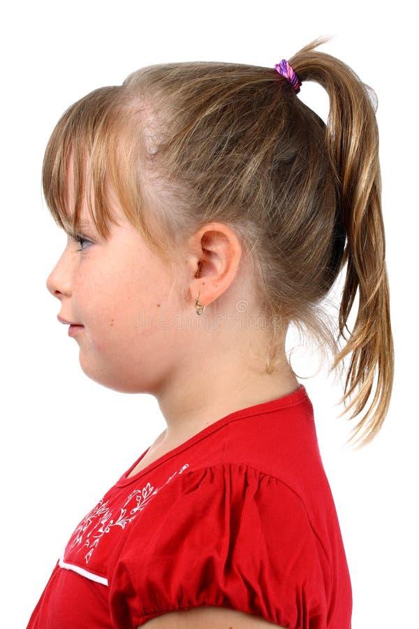 A menina pequena com cauda de pônei vestiu-se no vermelho isolado imagem de stock royalty free