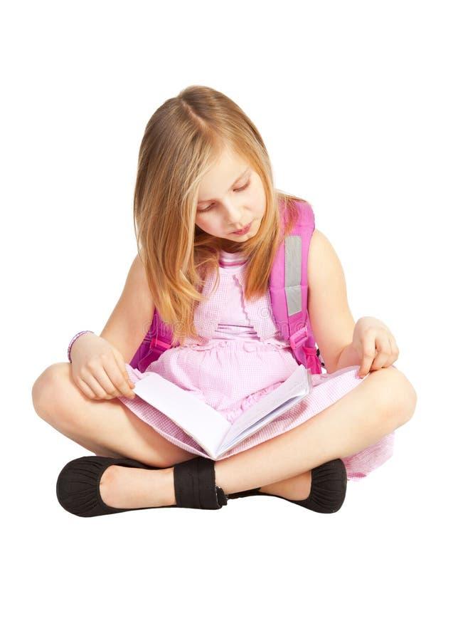 Menina pequena com a trouxa que faz trabalhos de casa sobre o branco fotos de stock