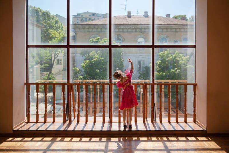 Menina pequena da bailarina do russo no exercício tradicional da barra do vestido perto da janela foto de stock