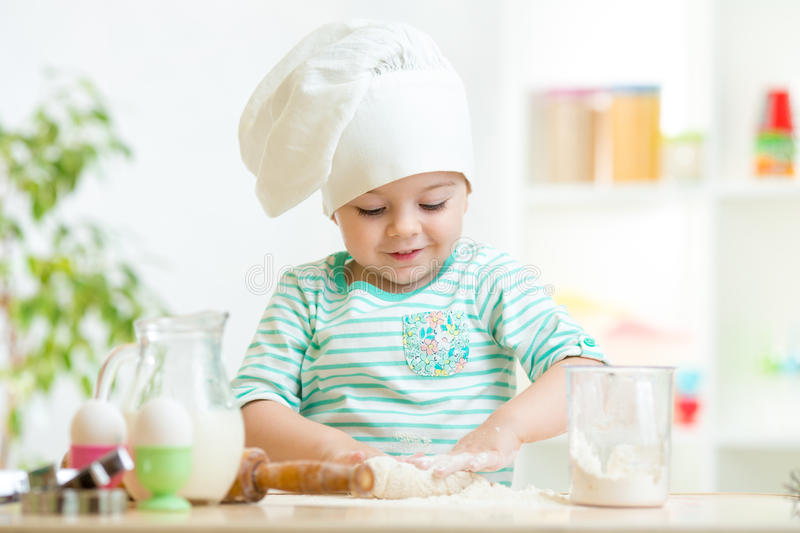 Menina pequena da criança do padeiro no chapéu do cozinheiro chefe fotos de stock royalty free